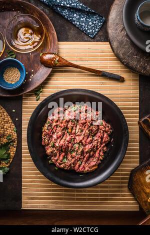 Fleischfüllung in schwarz Schüssel auf dunklen rustikalen Küche Tisch mit Schüsseln und Teller, Ansicht von oben - Stockfoto