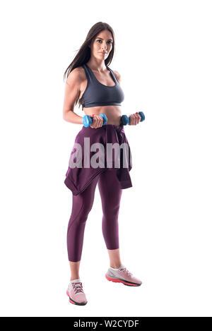 Athletische Passform junge Frau in Sportkleidung tun arme Bizeps Übungen mit Hanteln. Voller Körper auf weißem Hintergrund. - Stockfoto