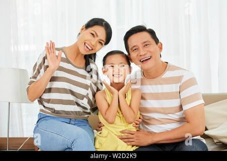 Portrait von glücklichen asiatischen Familie von drei Sitzen auf einem Sofa zusammen Posieren und lächelnd an der Kamera zu Hause. - Stockfoto