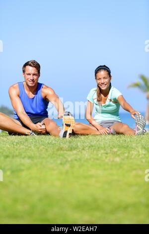 Fitness - paar Dehnübungen im Freien. Passen Mann und Frau tun Kniesehne bein Übung dehnen und strecken Training im Freien im Sommer. Schöne gemischtrassiges Paar. - Stockfoto