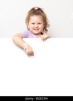 Lächelnd blue eyed kleines Mädchen spähen hinter einer weißen Tafel. - Stockfoto