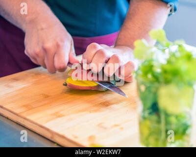 Nahaufnahmen der Hände des Menschen Vorbereitung von Obst und Gemüse in der modernen Küche. - Stockfoto