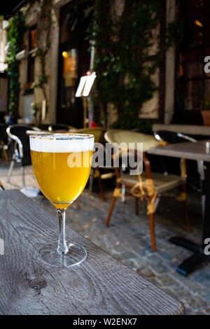 Berühmten belgischen Bier draußen serviert in kleinen alten Cafe in speziellen belgisches Bier Glas in der Sonne leuchtet