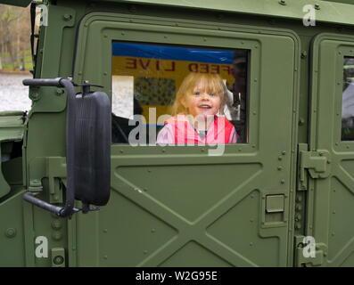 Meriden, CT USA. Apr 2019. Narzissenfest. Junge Mädchen in einem militärischen Humvee lächelnd an Soldat Vati. - Stockfoto