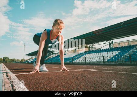 Bereit zu gehen. Junge fitness blonde Mädchen mit Spitze blau, schwarz Strumpfhose, Turnschuhe und Pony - Schwanz auf den Start des Stadions verfolgen, die Vorbereitung für eine - Stockfoto