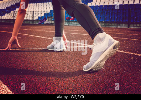 Bereit zu gehen. Junge Fitness Mädchen tragen Spitze blau, schwarz Strumpfhose, Turnschuhe und Pony - Schwanz auf den Start des Stadions verfolgen, die Vorbereitung für einen Lauf - Stockfoto