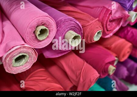 Mehrere bunte Stoffrollen liegen auf den Regalen in einer Lagerhalle. Sie sind Rosa, Violett, Rot, Blau und Grün. Closeup horizontale Foto wi - Stockfoto