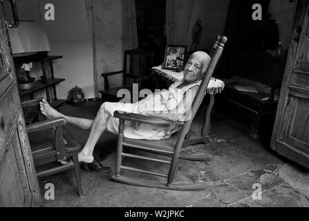 Trinidad Kuba: Die Dame ruht am Nachmittag in ihrem Schaukelstuhl, der darauf schaut, wie die Welt sie verpascht. Stockfoto