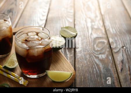 Gläser mit Eis, Cola, Kalk Schichten und Tubuli auf hölzernen Hintergrund - Stockfoto