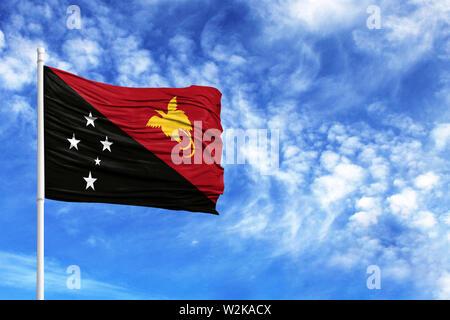 Nationalflagge von Papua Neuguinea auf einem Fahnenmast vor blauem Himmel - Stockfoto