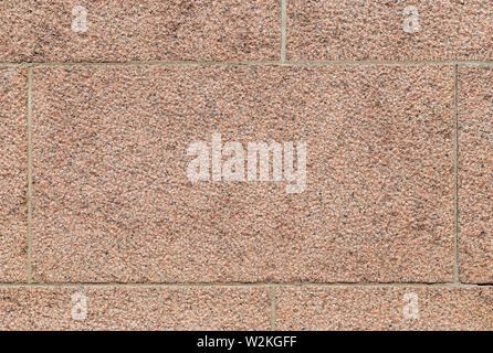 Close-up Teil einer holprigen Block aus rotem Granit stein Wand. Hochauflösende full frame Hintergrund Textur. - Stockfoto