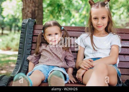 Zwei süße kleine Mädchen lächelnd und sitzen auf der Holzbank im Sommer Park - Stockfoto