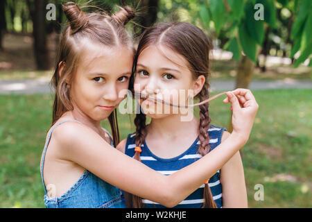 Zwei kleine Mädchen Spaß im Park im sonnigen Sommertag - Stockfoto