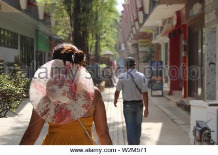 Frau in einem gelben Kleid mit einem schönen Blumenhut gehen auf die Einkaufszentren von einer Insel Resort. - Stockfoto