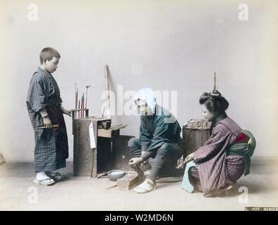 [1880s Japan - Japanische Leitung Mender] - ein Rohr mender trägt ein happi Fell arbeitet an einem kiseru Rohr, während eine junge Frau und ein Junge auf. 19 Vintage albumen Foto. - Stockfoto