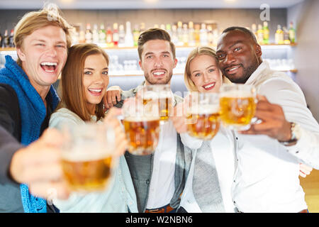 Lachend Gruppe von Freunden Bier trinken in der Kneipe in einer heiteren Stimmung - Stockfoto