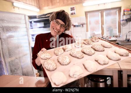 Stolz bio Bäcker Frau, Backblech voller Teiglinge bereit für den Backofen, die Herstellung von Brot, Greiling, Bayern, Deutschland - Stockfoto