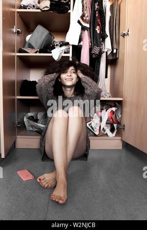 Junge Frau zu Hause vor der Garderobe sitzt, entscheiden, welches Outfit zu tragen - Stockfoto