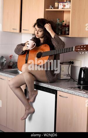Junge Frau mit Gitarre in der Küche zu Hause. - Stockfoto