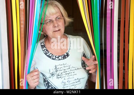Bigotten senior Frau Eröffnung bunten Vorhang - Stockfoto