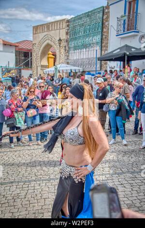Mertola, Portugal - 18. Mai 2019: hübsche Frau tanzen auf der Straße arabischen Tanz an das Islamische Festival in Mertola, einem wunderschönen portugiesischen Villag gehalten