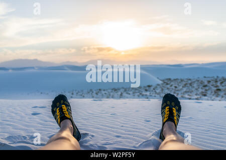 Die Beine der Frau Wasser schuhe Lügen sitzen in White Sands Dunes National Monument in New Mexico mit Blick auf den Sonnenuntergang über dem Horizont - Stockfoto