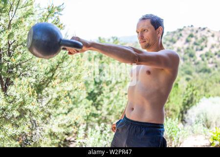 Junge passen shirtless Mann Training mit schweren kettlebell, Swing und Muskeln im Freien außerhalb Park holding Gewichtheben - Stockfoto
