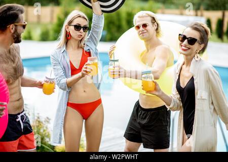 Gruppe von Freunden eine Party, tanzen und trinken Saft in der Nähe der Pool im Sommer - Stockfoto