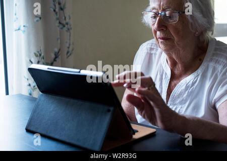 Nahaufnahme der älteren Frau an einem Tisch sitzen, mit einem digitalen Tablet, über den Touchscreen. - Stockfoto