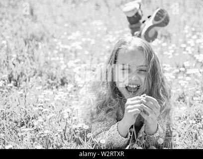 Mädchen liegt auf Gras, grassplot für den Hintergrund. Kind genießen Sie Frühling sonniges Wetter beim Liegen an der Wiese mit Tender daisy flowers. Empfindlichkeit Konzept. Mädchen auf glückliches Gesicht hält daisy flower. - Stockfoto