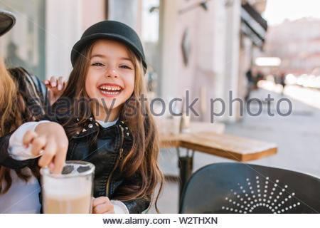 Portrait von ein fröhliches kleines Mädchen sitzen auf der Straße in der City Cafe mit Mama. Sie ist Aprilscherze mit Kaffee, gute Laune, stilvoll gekleidet. Für text - Stockfoto