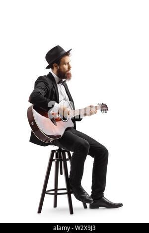 Volle Länge geschossen von einem Mann auf einem Stuhl sitzen und spielen eine akustische Gitarre auf weißem Hintergrund - Stockfoto