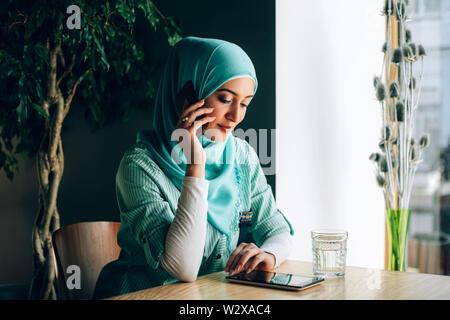 Schöne junge arabische Mädchen im hijab Gespräch per Telefon im Cafe. - Stockfoto