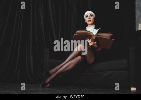 Schöne junge Nonne in Religion schwarzen Anzug hält Bibel und auf Kamera posieren mit großen Buch auf einem schwarzen Hintergrund. Religion Konzept. - Stockfoto
