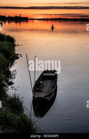 Boote und Fischer fischen an einem ruhigen Sommer Abend bei Sonnenuntergang auf dem Fluss Loire in Frankreich