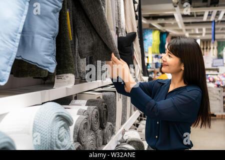 Asiatische Frauen entscheiden sich für einen neuen Teppich in der Mall zu kaufen. Einkaufsmöglichkeiten für Lebensmittel und Haushaltswaren sind in Märkte, Supermärkte oder großen Shopping Cent erforderlich - Stockfoto