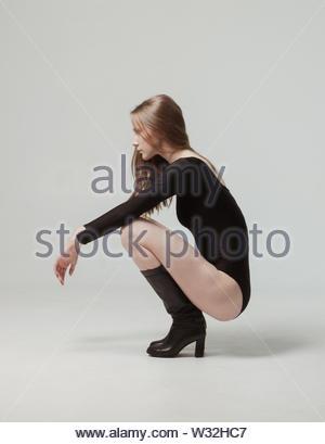 Blond Woman in Black body und Stiefel hocken im Studio - Stockfoto