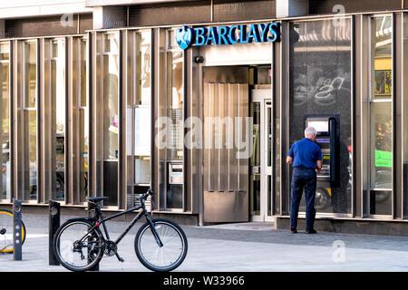 London, Großbritannien - 13 September, 2018: Mann auf der Straße Bürgersteig der Barclays Bank abheben, wodurch Bargeld aus Geldautomaten - Stockfoto