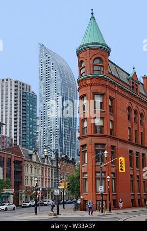 TORONTO - Juli 2019: viktorianischen Gebäude, darunter die Gooderham Flatiron und Gusseisen Gebäude, mit modernen Wolkenkratzern im Hintergrund. - Stockfoto