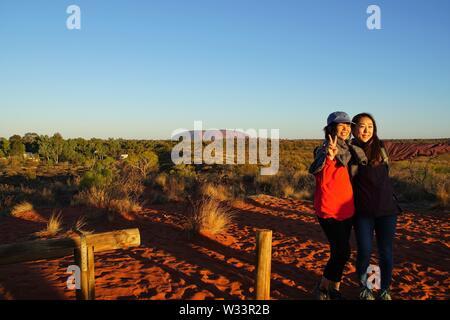 Am späten Nachmittag Sonne leuchtenden zwei junge Frauen posieren für ein Foto mit Uluru im Hintergrund - Stockfoto