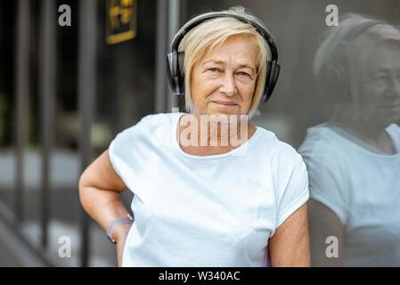 Porträt eines aktiven älteren Frau im Sport Kleidung stehend mit Kopfhörer im Freien. Konzept für einen gesunden Lebensstil im Ruhestand