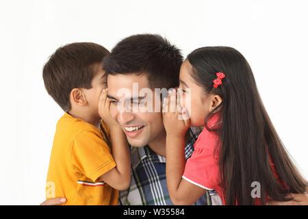 Junge und Mädchen flüstern ihrem Vater ins Ohr