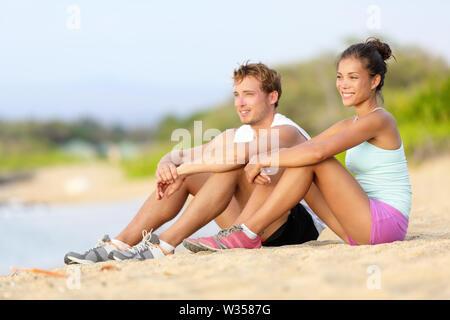 Sportliche Läufer ruhend sitzen vor am Strand laufen. Die Athleten laufen Paar Mann und Frau eine Pause nach dem Joggen. Fit Sport Fitness Ehepaar gesunden, aktiven Lebensstil. - Stockfoto