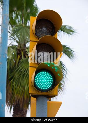 Eine Ampel zeigt Grün mit Palmen in den Straßen von Barcelona. - Stockfoto