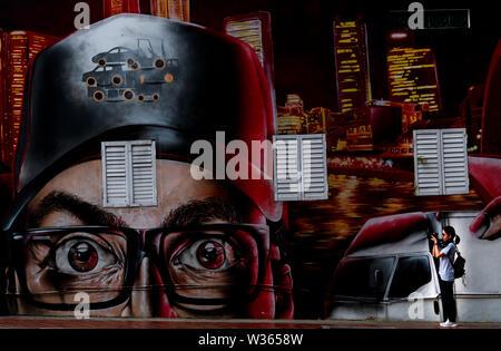 Singapur - 19. MAI 2019: asiatische Frau Tourist, Foto street art Graffiti an Singapur Sehenswürdigkeiten in der Nähe von Singapore River. Beton Wand von Gebäude - Stockfoto