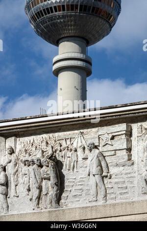 Relief auf Gebäude aus der Zeit der kommunistischen Osten Deutschland Berliner Fernsehturm, Alexanderplatz mit Symbolen von Stern-, Sichel und Hammer - Stockfoto