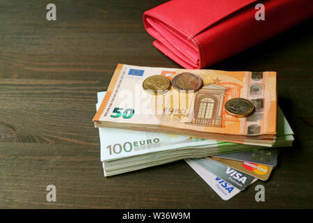 Euro-banknoten und -Münzen mit verschiedenen Kreditkarten und eine rote Mappe im Hintergrund - Stockfoto