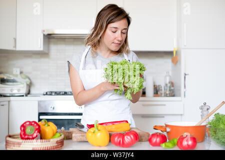 Junge Frau Vorbereitung grünen Salat essen in der Küche zu Hause - Stockfoto