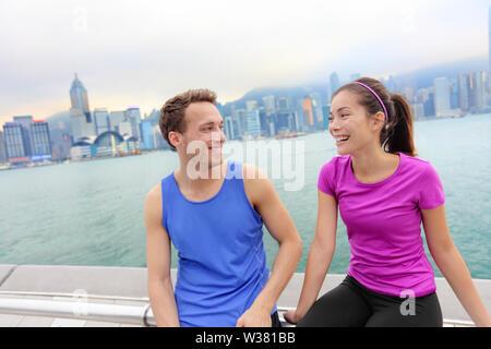Läufer Entspannung nach Training in Hong Kong City. Läuft der kaukasischen und asiatischen Mann und Frau Post laufen eine Pause zusammen gesprochen auf der Avenue der Stars im Victoria Harbour und die Skyline von Hongkong. - Stockfoto