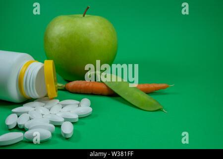 Pillen aus einer weißen Flasche in der Nähe von Apple, pea Pod und Karotte auf grünem Hintergrund. Healthcare, Diät oder Gewichtsverlust Konzept - Stockfoto